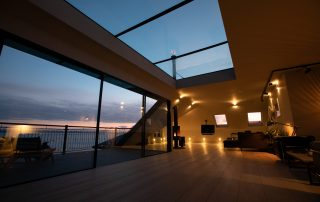 view of lounge and balcony at night in The Penthouse